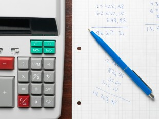 calculator next to paper with numbers written on and a pen