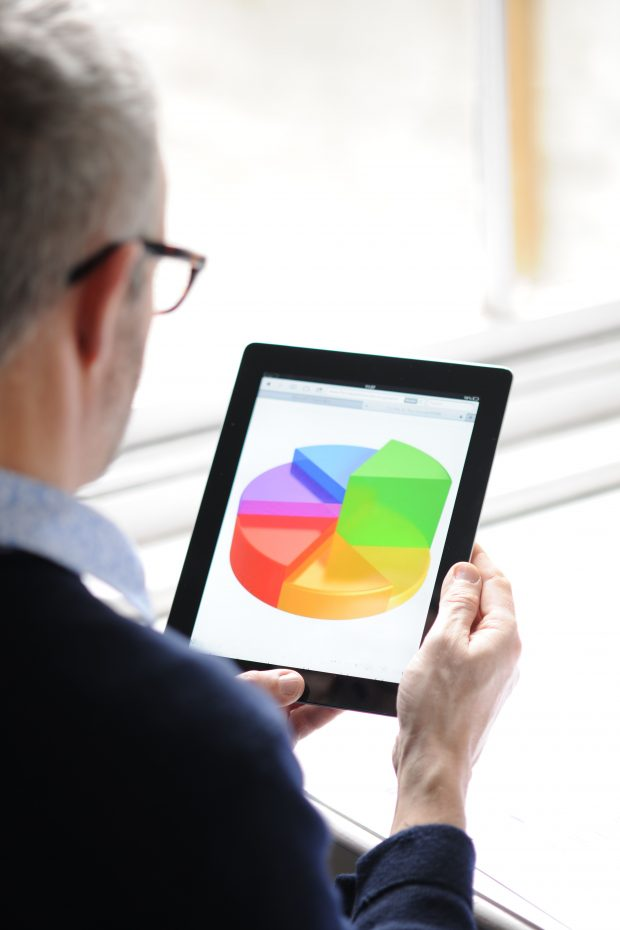 man looking at a tablet with a pie chart displayed