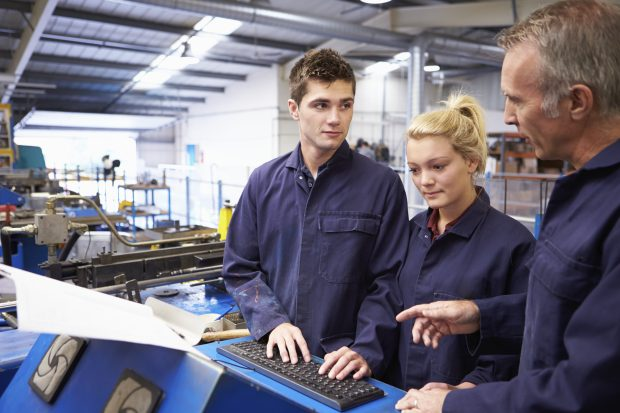 Apprentices listening to their supervisor in a workshop