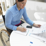 Lady in wheelchair, at a table looking at statements