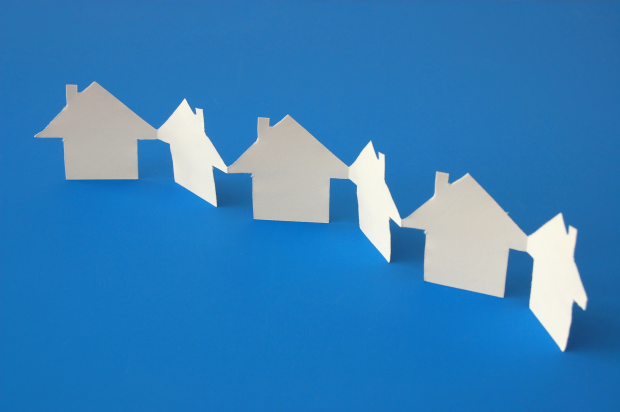 paper chain of white houses on a blue background