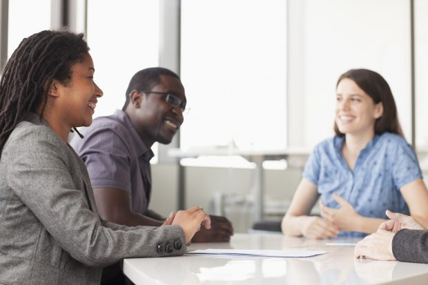 Two women and a man smiling in a team meeting
