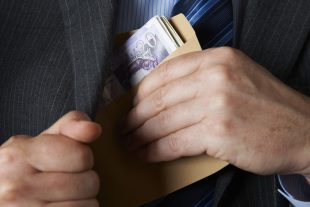 Business man putting an envelope full of money into his inside pocket