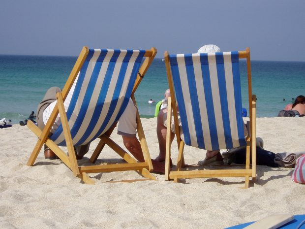 Two people sitting in deckchairs at the seaside