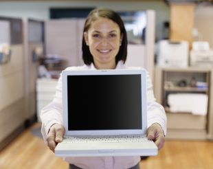 Businesswoman holding laptop, smiling towards the camera