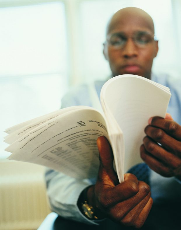 Man sitting down, reading documents