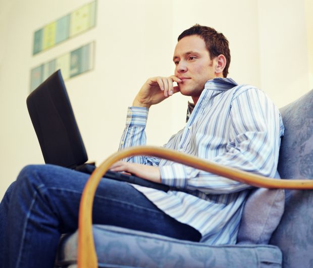 Man sat on chair looking at laptop