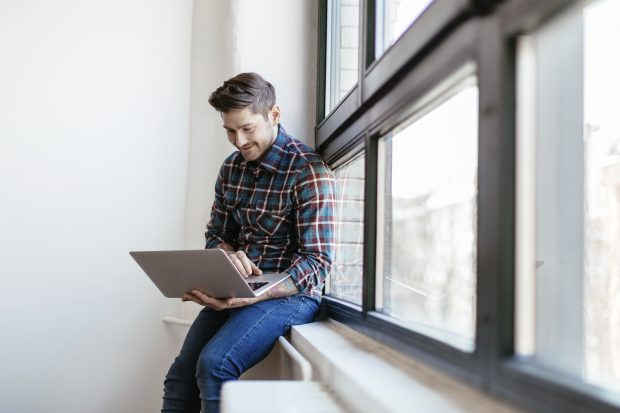 man sat on a window ledge, using a laptop and smiling