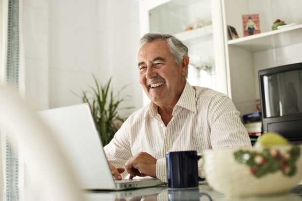 man, smiling using a laptop