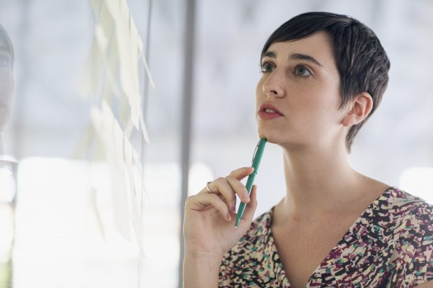 woman thinking and looking at whiteboard
