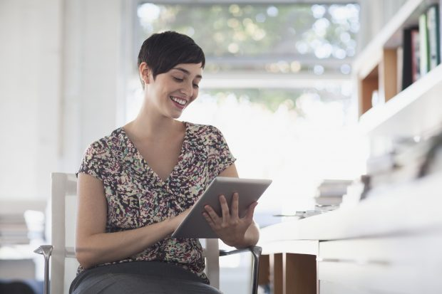Woman sitting in a chair, smiling and working on a tablet device