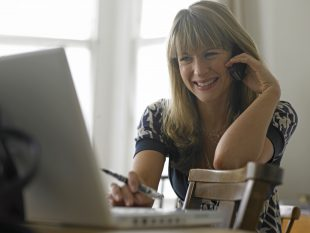 Smiling lady on a phone using a laptop
