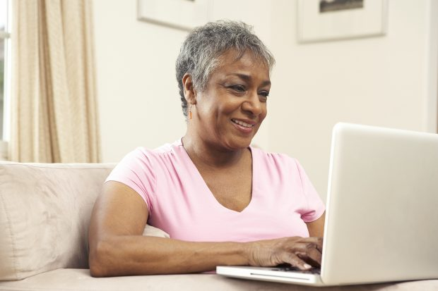 A smiling woman using a laptop