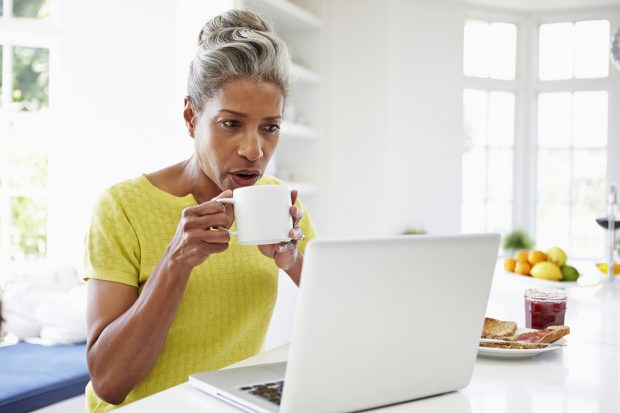 woman having breakfast looking at laptop