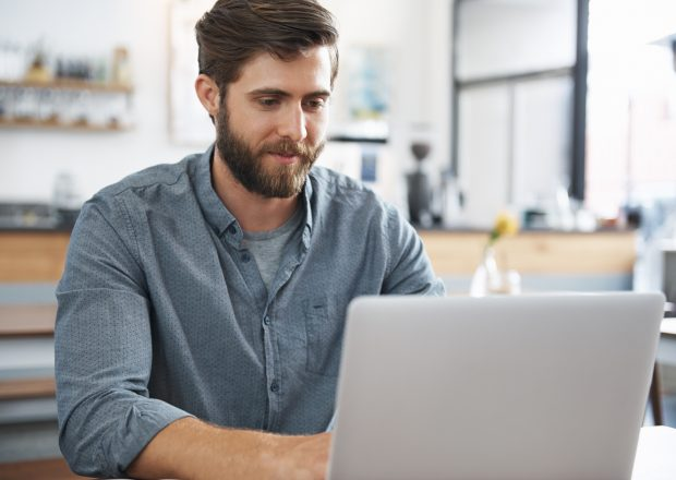 Smiling man sitting in a cafe, using a laptop