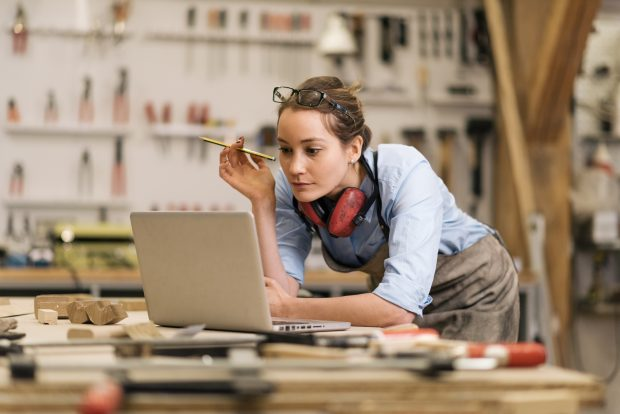 Female carpenter looking at a laptop on a work bench