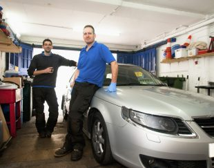 Two mechanics in a garage, leaning against a car