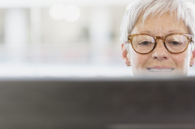 Smiling businesswoman wearing spectacles, looking at a computer screen