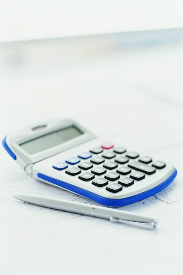 calculator and pen on top of document