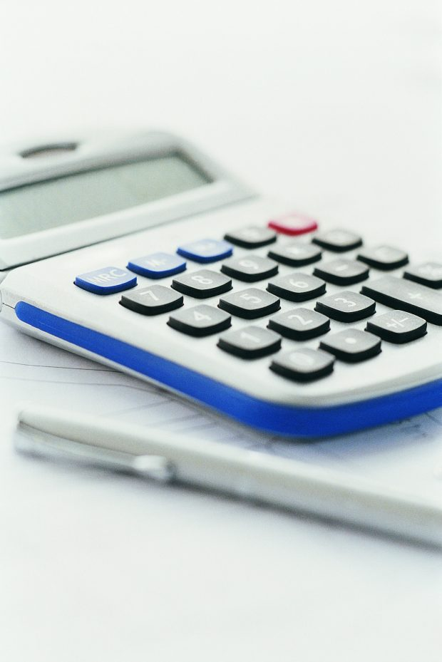 calculator and pen on top of documents