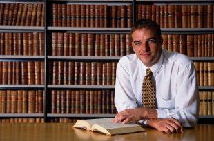smiling man, looking at a book in an office library