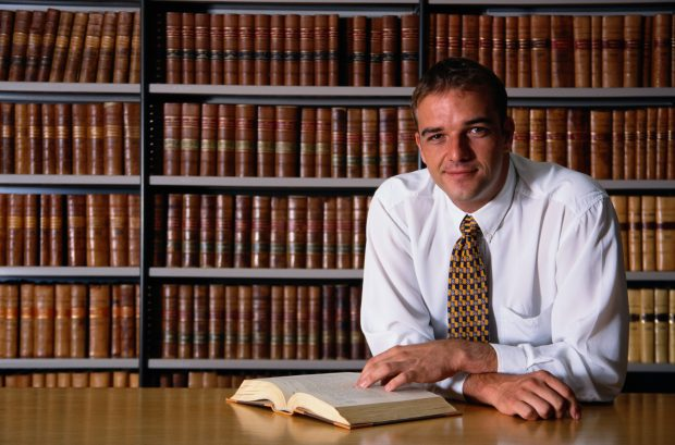 smiling man looking at a book in a office library