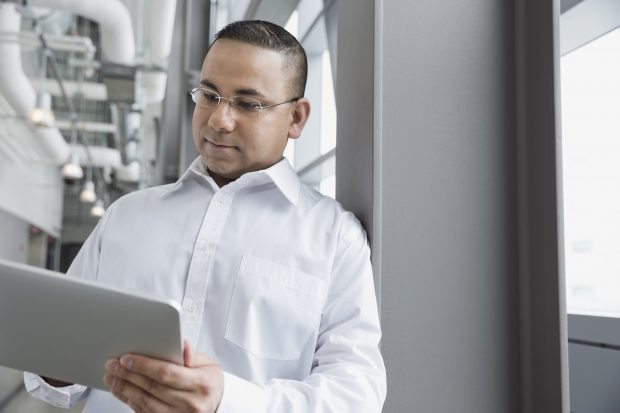 Man leaning against a workplace wall looking at a tablet device