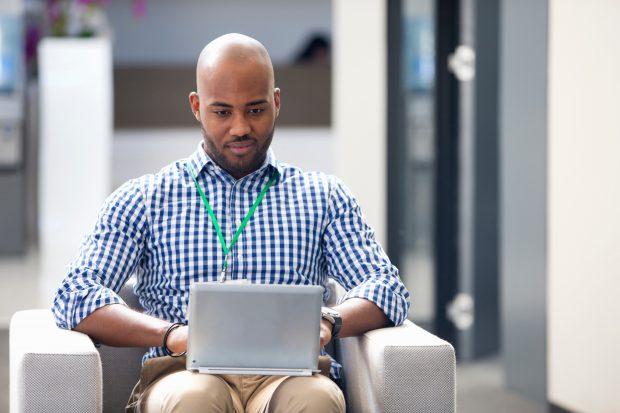 man sitting down looking at his laptop