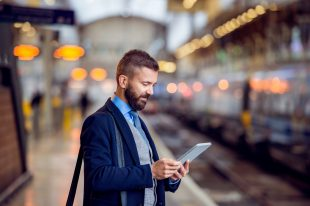 business man at train station reading tablet