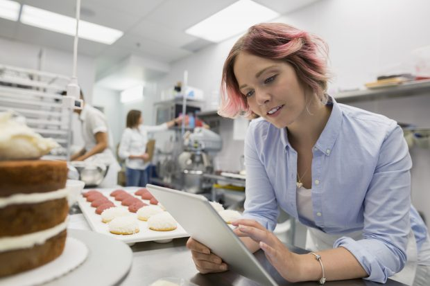 pastry chef looking at a digital tablet