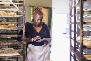 Female baker using a digital tablet in a bakery