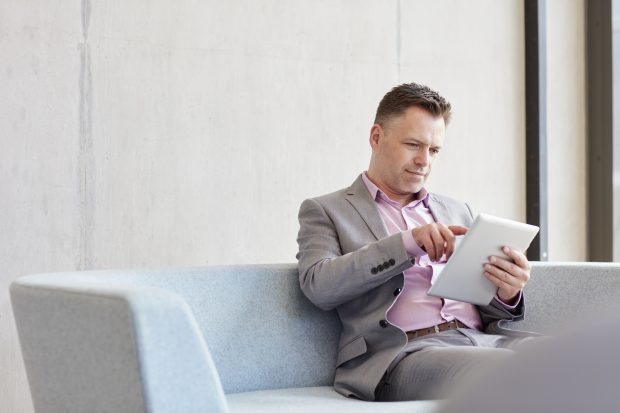 Businessman using a digital device, sitting on a sofa
