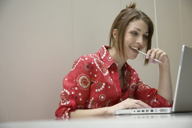 Woman smiling and looking at her laptop