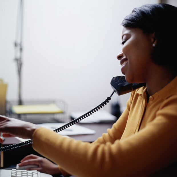 Smiling woman on the phone and working at her computer
